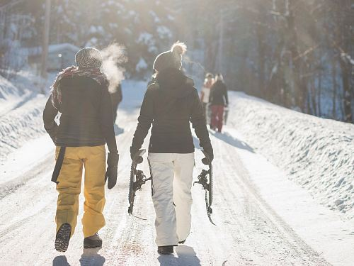 person holding snow ski blades while walking on snowy mountain during daytime