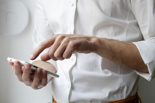 photo person holding white Android smartphone in white shirt free for commercial use images