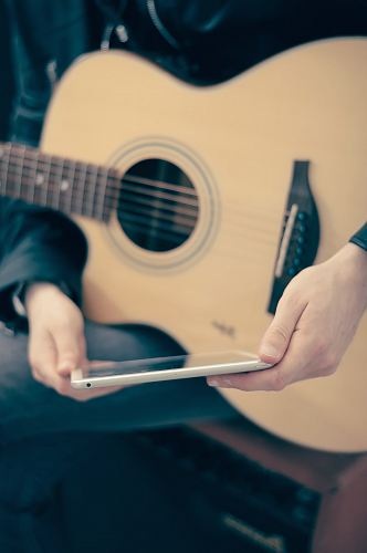 photo person with guitar on lap holding tablet free for commercial use images
