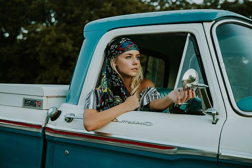 photo photography of woman holding side mirror in white and green 2-door pickup truck free for commercial use images
