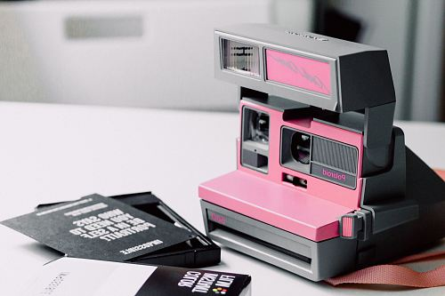pink and gray Polaroid instant camera on white wooden surface