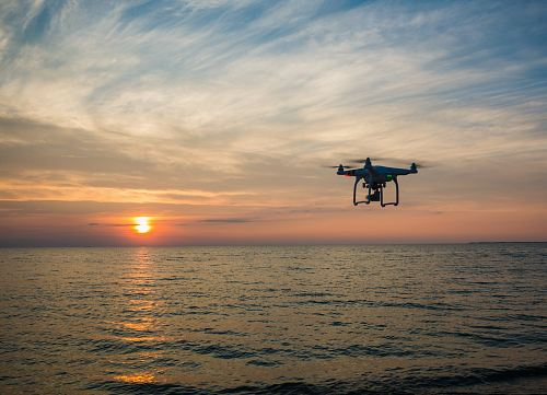 photo quadcopter flying over body of water free for commercial use images