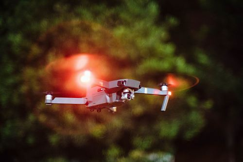 photo selective focus photography of drone flying on mid-air during nighttime free for commercial use images