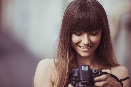 selective focus photography of smiling woman holding camera