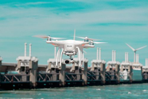 photo selective focus photography of white drone hovering above body of water free for commercial use images