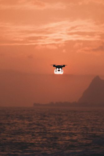 photo silhouette of drone hovering above body of water free for commercial use images