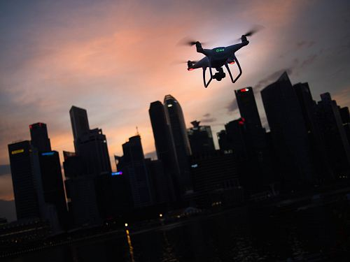 photo silhouette of quadcopter drone hovering near the city free for commercial use images