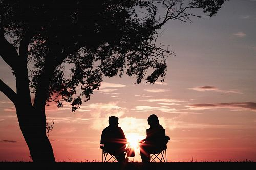 photo silhouette of two person sitting on chair near tree free for commercial use images