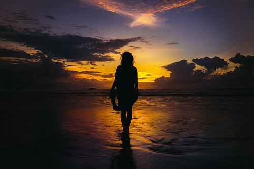 photo silhouette of woman standing on seashore free for commercial use images
