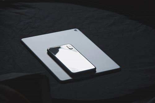 space gray iPhone X on tablet computer