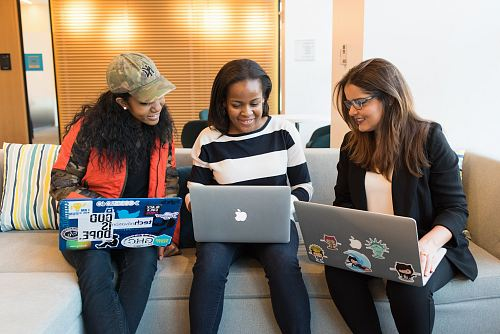 three women sitting on sofa with MacBook