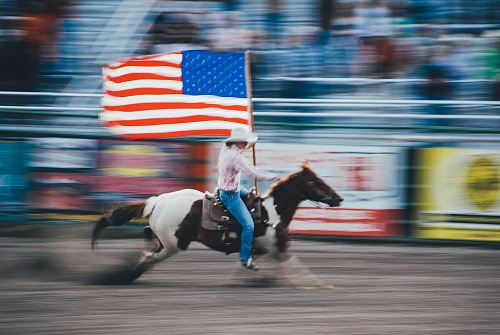 photo time lapse photo of man carrying U.S. flag while riding brown horse free for commercial use images