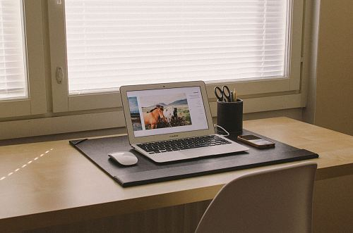 photo turned on MacBook on beige wooden desk free for commercial use images