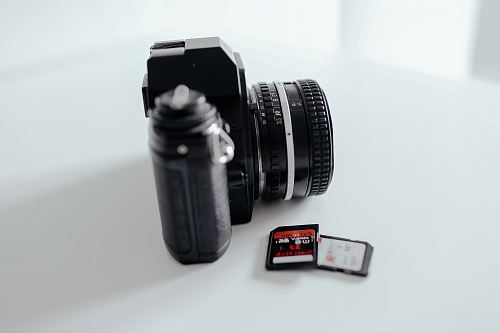 two black memory cards beside black DSLR camera on white surface