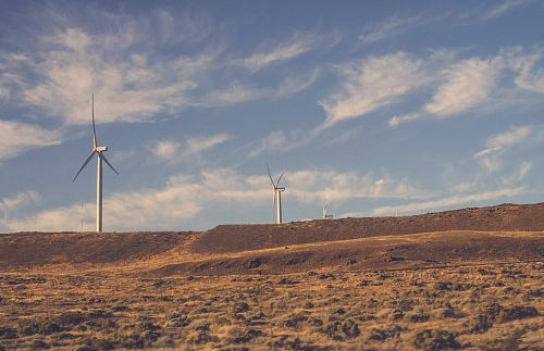 two gray wind turbines under cloudy blue sky during daytime