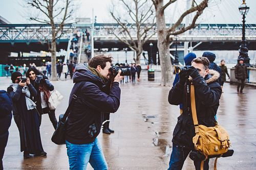 two men facing each other taking photo in black DSLR camera during daytime