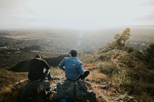 photo two person sitting on rock free for commercial use images