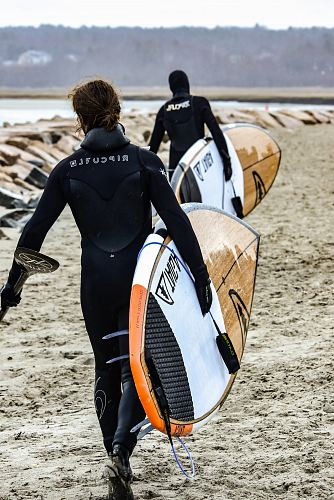 photo two person walking towards body of water while carrying surfboards free for commercial use images