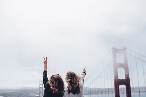 two women making peace sign near the Golden Gate bridge