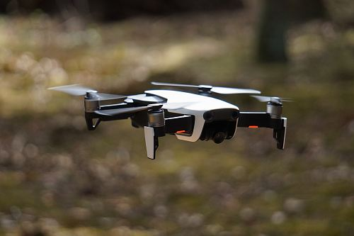 white and black quadcopter hovering on grass