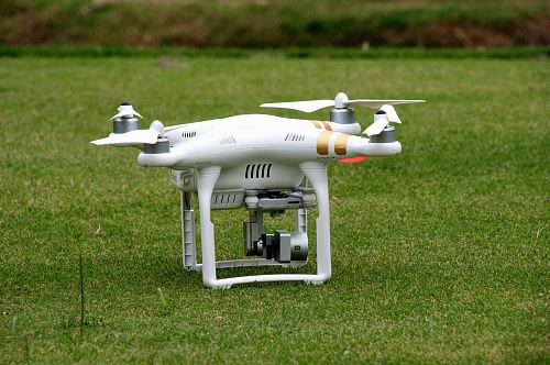 white quadcopter on lawn