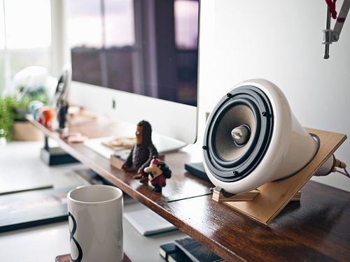 white speaker in brown holder beside silver Imac