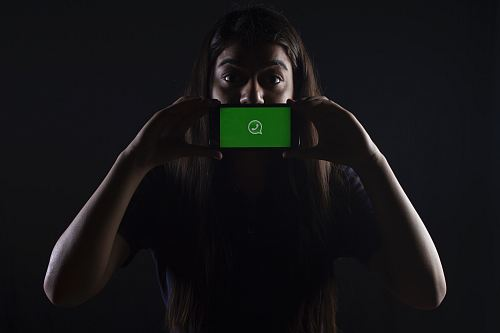 woman holding black smartphone at Whatsapp logo