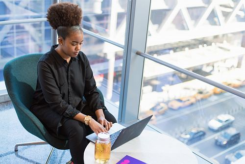woman in black dress shirt using MacBook
