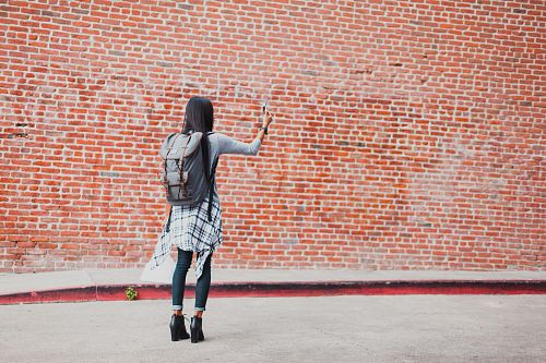 photo woman standing beside cinder brick wall while using smartphone free for commercial use images