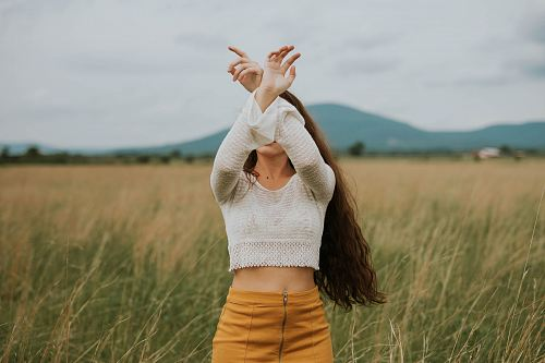 woman wearing gray crop top sweater on grass field