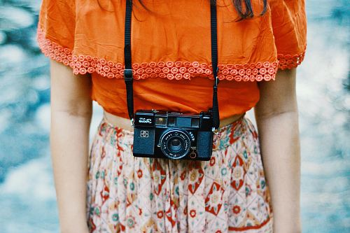 photo woman wearing orange and multicolored dress with black bridge camera on her neck free for commercial use images