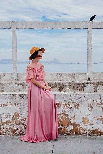 photo woman wearing pink dress standing next to white wall free for commercial use images