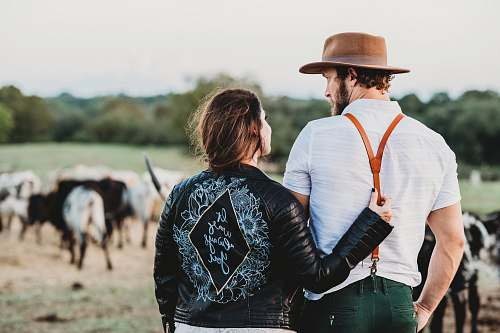 clothing man and woman on green field with cattles person