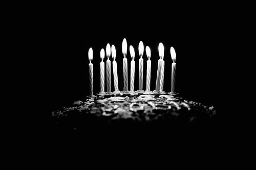 candle grayscale photography of lighted birthday candles birthday cake