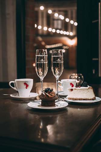 dessert two champagne flute glass beside sliced cake and cupcake roma cafe
