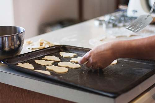 food person lining assorted-shaped cookies on baking sheet inside kitchen bake