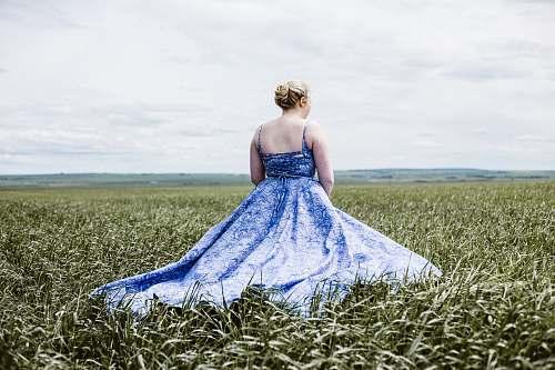 apparel woman standing on green grass field gown