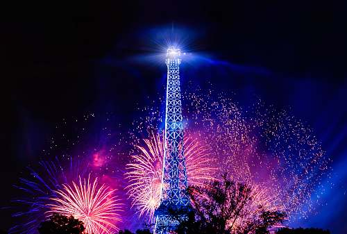 night photo of eiffel tower with fireworks background outdoors