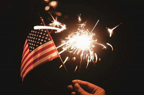 flag time lapse photography of sparkler and U.S.A flag let independence day