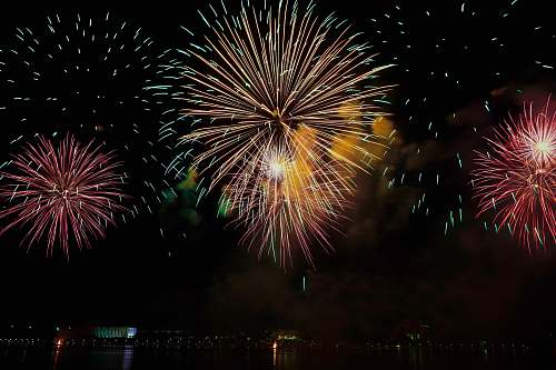 night yellow and pink fireworks display in sky outdoors