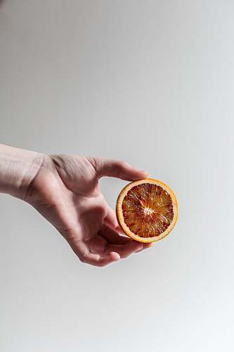 person person holding sliced grapefruit human