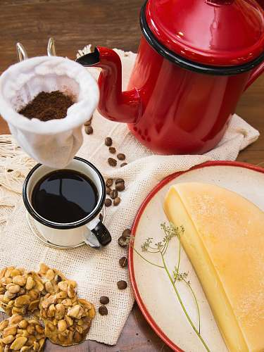 fondue red and black kettle near mug filled with coffee and half a cheese on table state of minas gerais