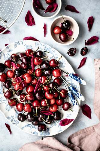 photo fruit red cherry fruits on oval white and blue floral ceramic plate cherry free for commercial use images