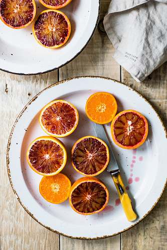 bowl sliced oranges on white plate plate
