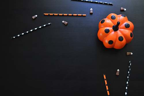 pumpkin orange and black polka-dot pumpkin toy on black table pumpkin flat lay