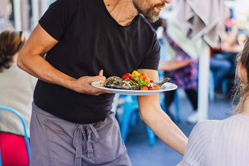 person man standing and holding plate food