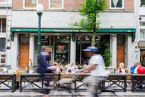 restaurant timelapse photo of person riding bike passing by storefront during daytime cafe