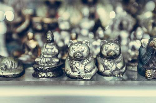 art close-up photography of silver-colored bear and Buddha figurines ubud