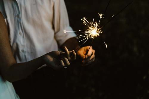 fire two person holding sparklers hand