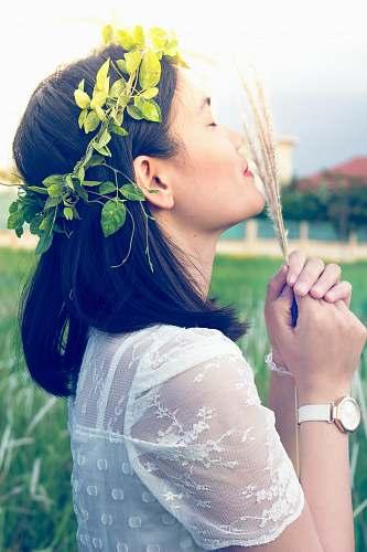 human close photography of woman holding fern woman